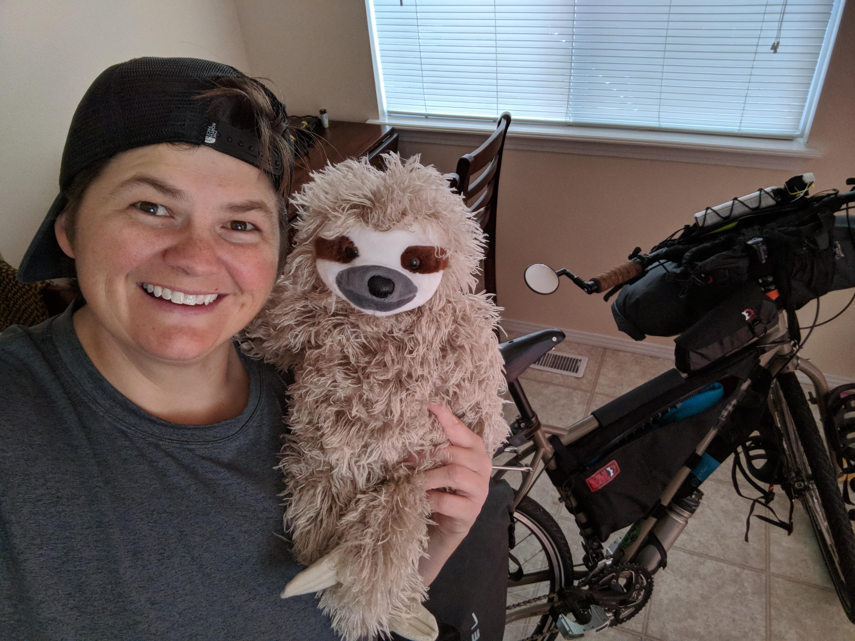 Jenni and Sammy (our stuffed sloth mascot) pose by their bike