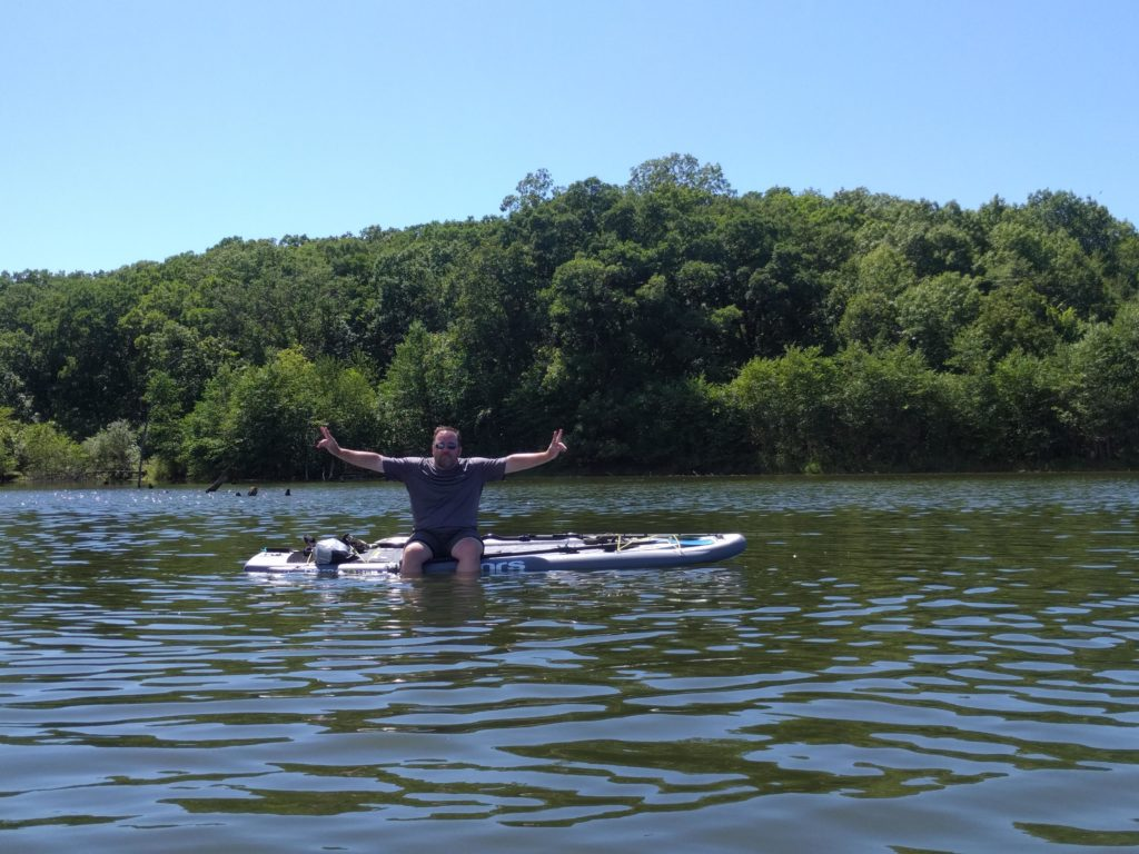 Eric sitting on paddle board with legs in water with both hands up flashing the peace sign.