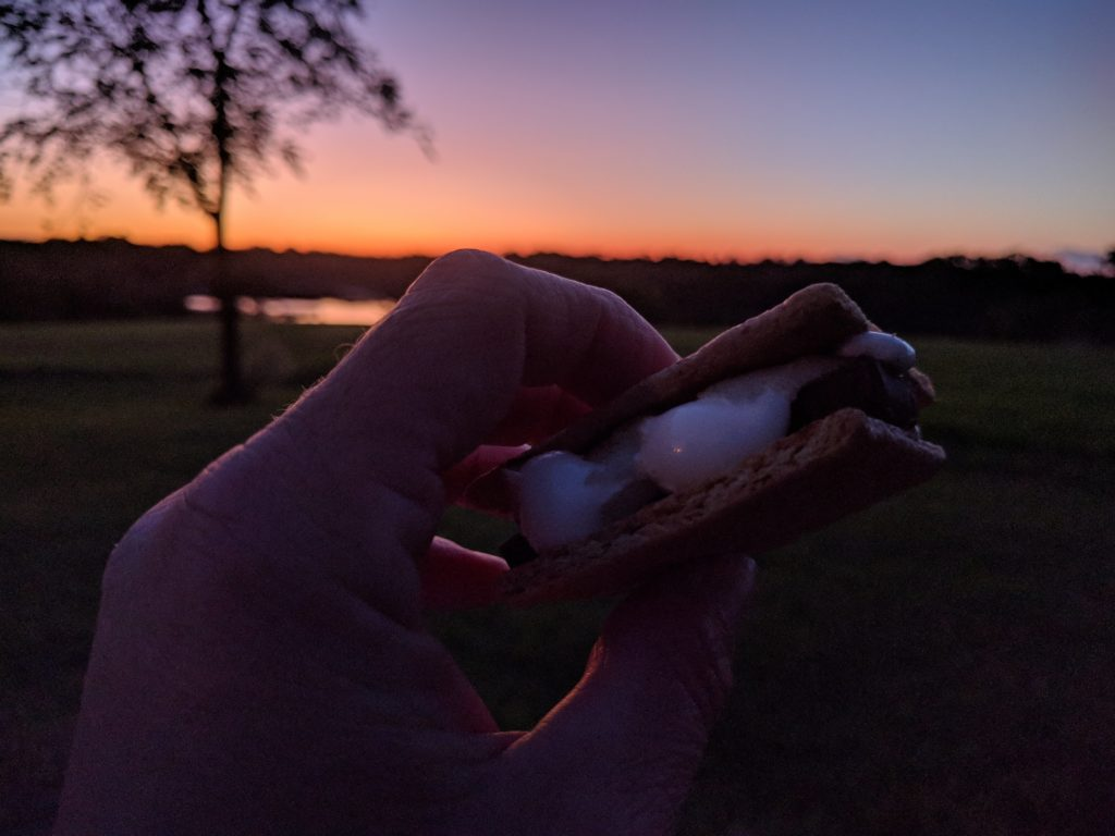 Sunset in the background and a hand holding a melting s'more treat in the foreground