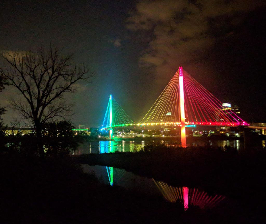 same bridge, now with pink, yellow, green, and blue colors with lights reflecting on the river below