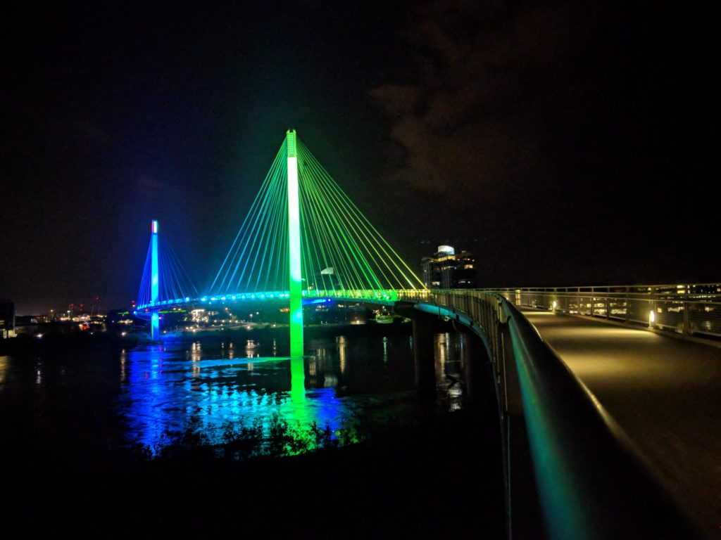 A large pedestrian bridge lit up with colors of yellow/green and blue