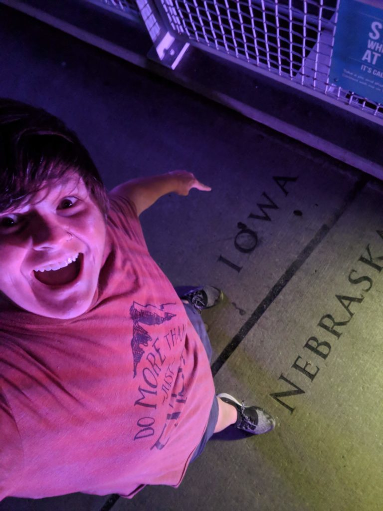 Selfie of Jenni as she stands with one foot in Iowa and one foot in Nebraska on top of the pedestrian bridge.