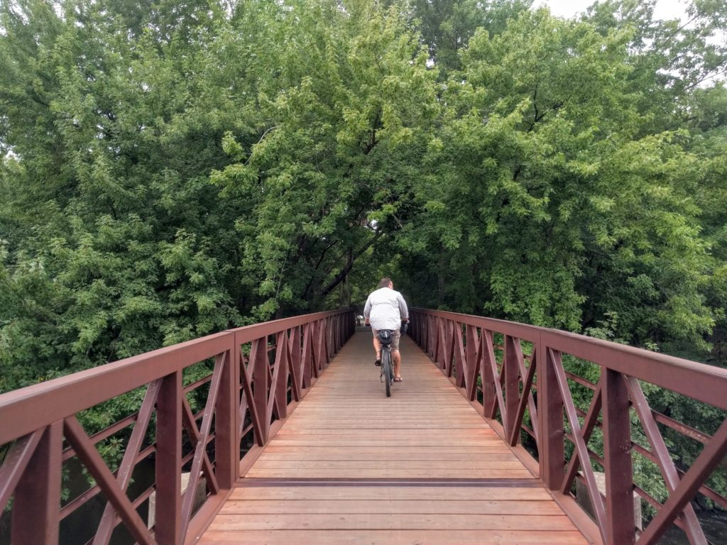 Eric riding bike across a red bridge into a tunnel of trees