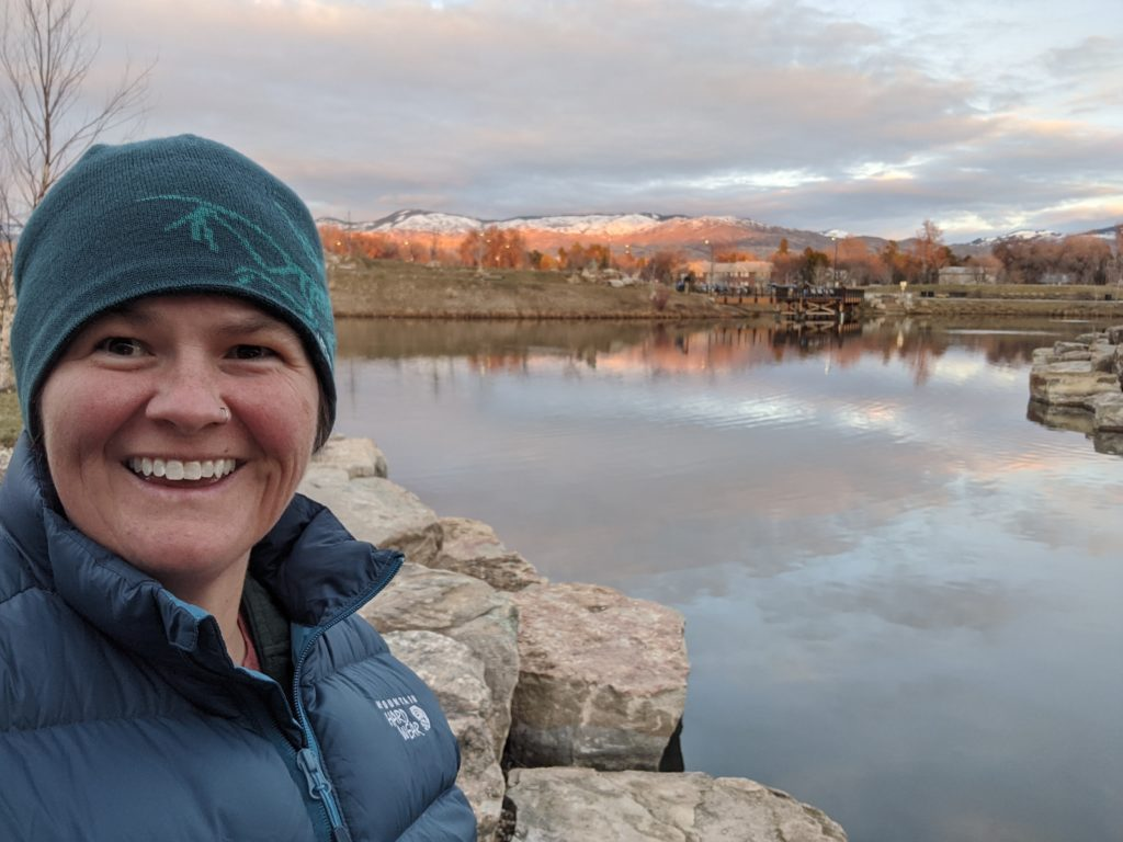 Me smiling  with a view of lake and foothills in the background. Photo from a walk.