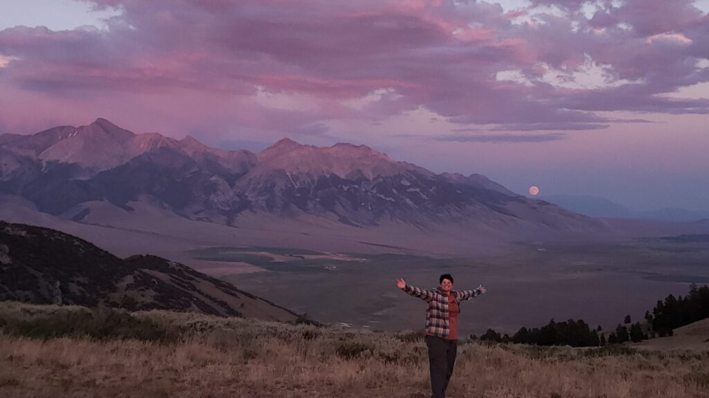 Jenni with her arms raised high celebrating the purple sunset over the mountain with a full moon rising.