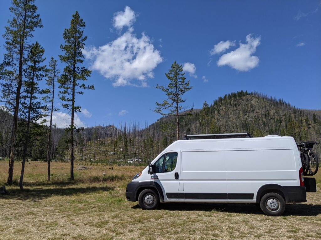 A side view of the van with large hills and lot of trees in the background.