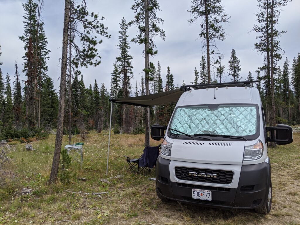 The van with the awning out, trees in the background.