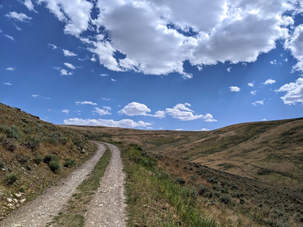 Gravel road with bright blue sky and white puffy clouds in the background.