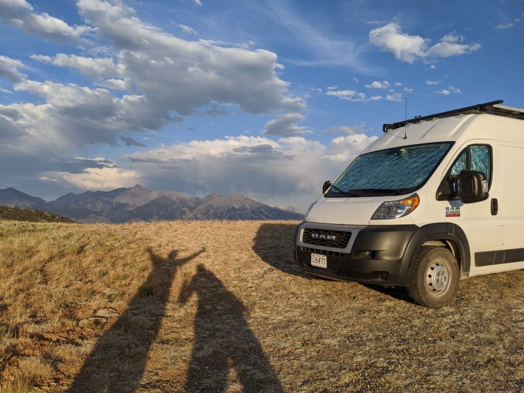 Jenni and Eric's shadow with the van and an epic mountain scene in the background.