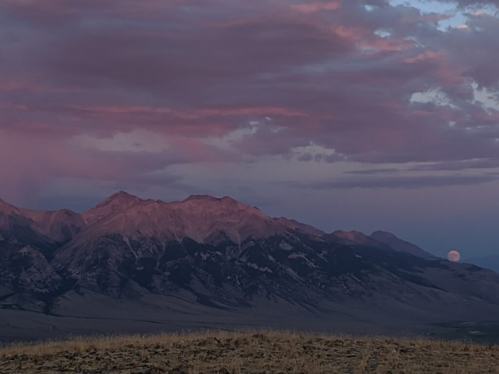 Purple sunset over mountain with full moon rising up.