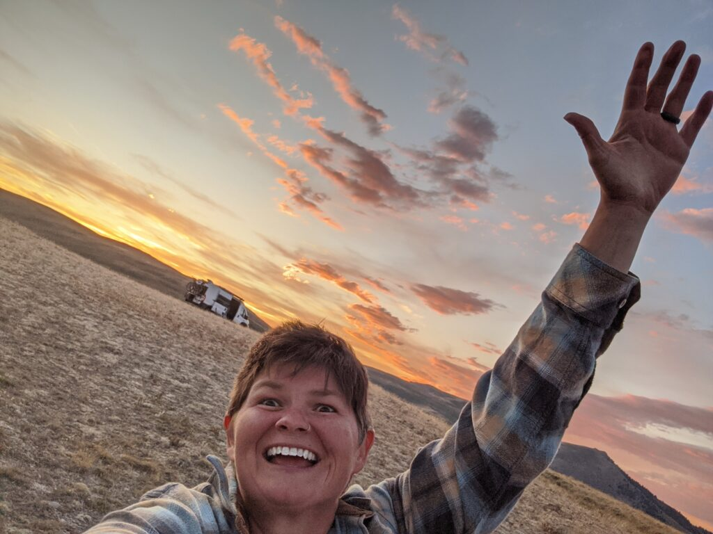 Jenni looking wildly happy with the van and a beautiful sunset in the background.