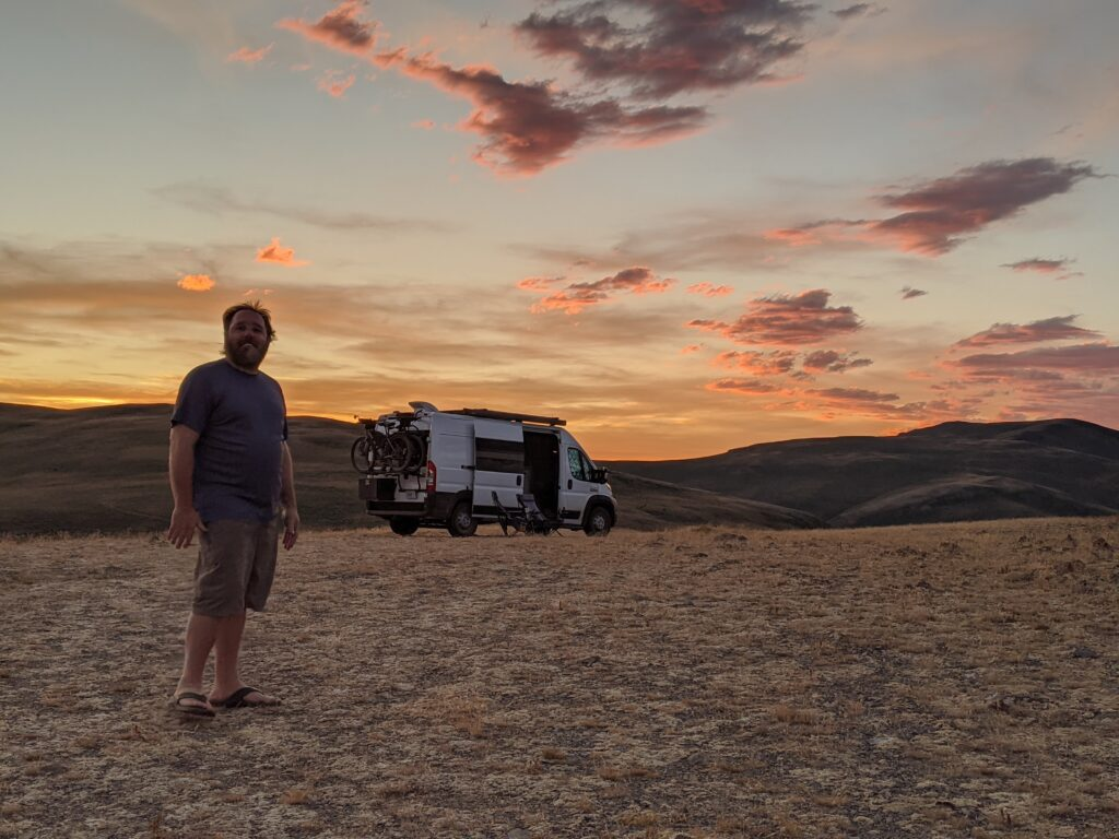 Eric smiling with the van and a sunset in the background.