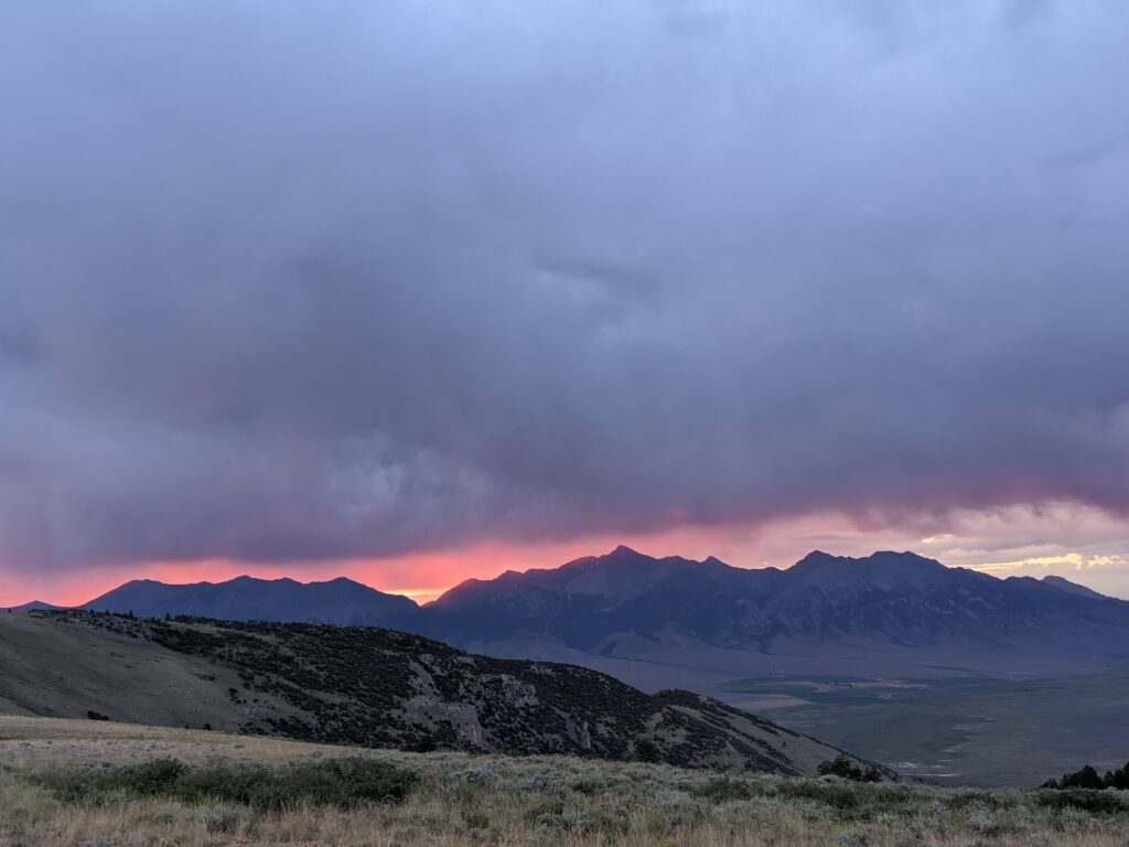 A vibrant pink and dark blue dramatic sunrise over the mountains.
